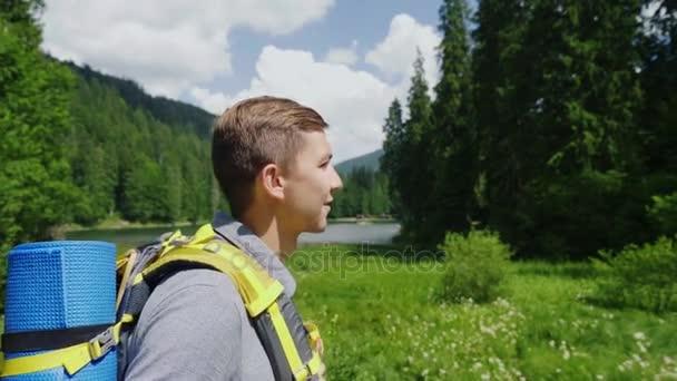 Atraktivní turistické muž jde do malebné místo na pozadí louky, hory a nebe. Turistika a aktivní životní styl