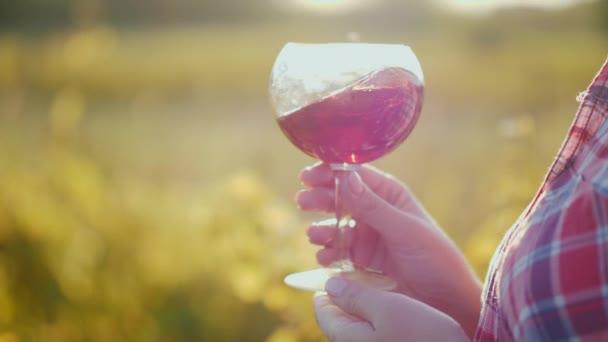 Ruce drží sklenku vína. Venku ochutnávka