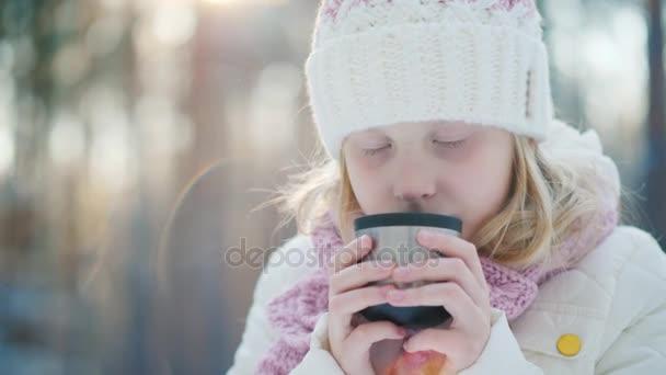 6 let stará dívka pije horký čaj na ulici. Na pozadí zimní les