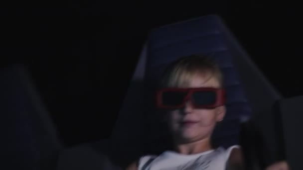The child is watching a 3D movie in the cinema with special effects and  moving chairs
