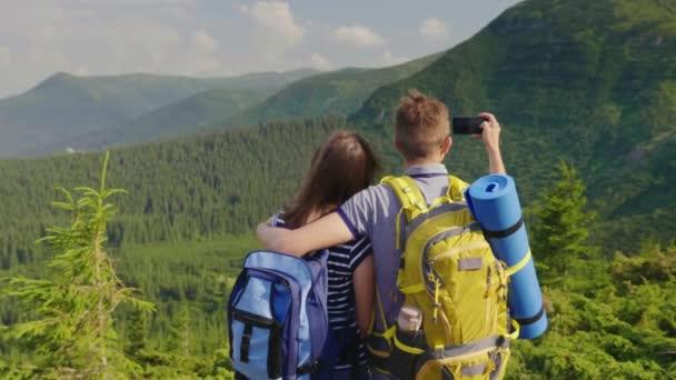 Freunde fotografieren eine herrlichen Berglandschaft. Genießen Sie den Rest zusammen. Ansicht von hinten