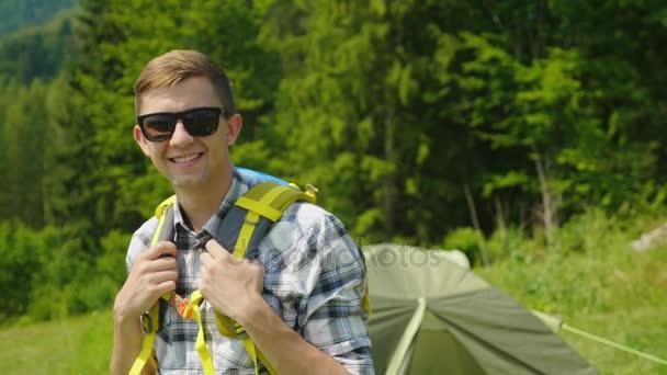 Portréja egy boldog férfi utazó. Mosolyogva nézi a kamerát, a kempingben a sátor közelében
