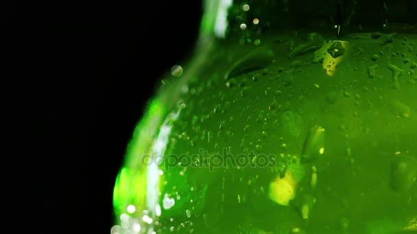 Primo piano di un pezzo di una bottiglia di birra. Le compresse sono coperti. Combatte contro uno sfondo nero. Placare il tuo concetto di sete