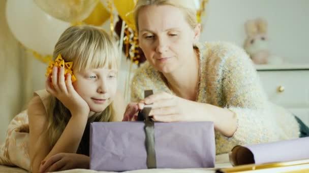 Žena s dítětem je balení dárků pohromadě. Připravujeme překvapení