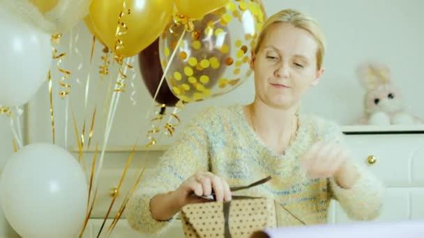 Žena se připravuje dárky pro dětské narozeniny. Obtéká pole v papíru, spojuje stuha