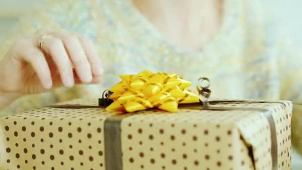 Ženské ruce upravit pás karet a luk, na krabici s dárkem. Detail