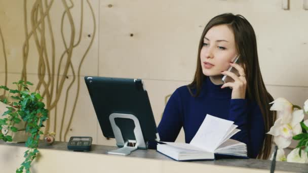 The secretary in a small office speaks on the phone, makes notes in the tablet