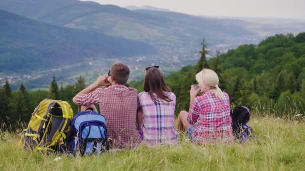 Három barát pihenni, festői környezetben. Ők ülnek körül a hátizsákok, teát inni. Aktív életmód és utazási koncepció