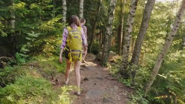 Nézet hátulról: egy pár turista hátizsákok, megy egy festői hegyi ösvényen. A lenyugvó nap sugaraiban