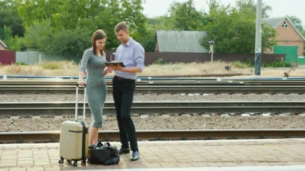 Ein Mann und eine Frau stehen auf einem Bahnsteig im Grünen. Tablet verwenden