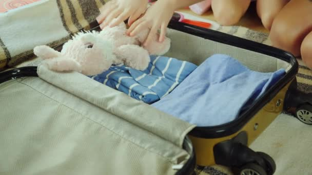 Mutter und Kind gehen auf eine Reise. Zusammengestellt von Sachen und Spielzeug in einer Reisetasche
