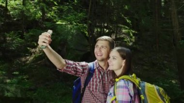 An attractive couple of tourists are photographed in the forest. Selfie with backpacks on a hike