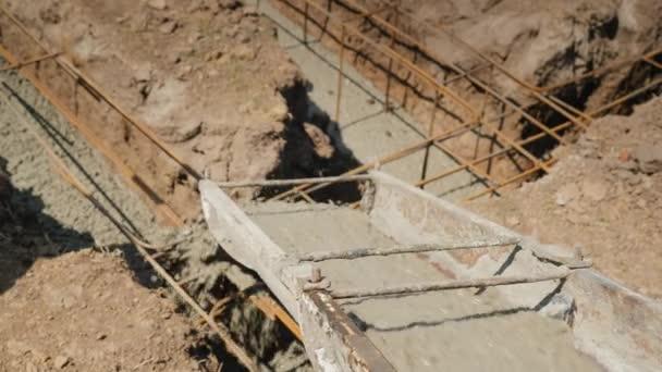Ansicht von oben: Beton fließt durch das Rohr in das Fundament des Untergeschosses. Bau von Ferienhäusern Konzept