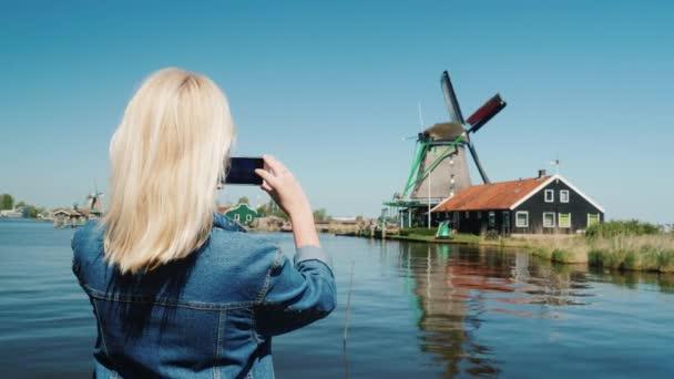 A woman tourist takes pictures of old windmills in Holland. Travel and Tourism in Europe