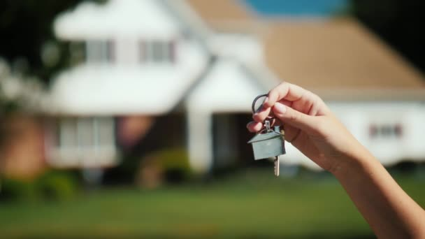 The hand holds the keys to the house. Against the background of a slightly blurred typical American house