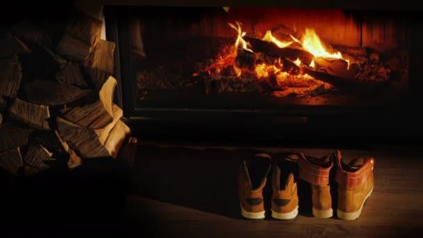 Horní pohled na pánské a dámské zimní boty suché u krbu. Romantický zimní večer