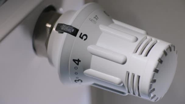 der Hausbesitzer stellt die Temperatur im Haus auf einem Thermostat ein