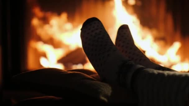 Legs in socks are heated by the fireplace in winter evening
