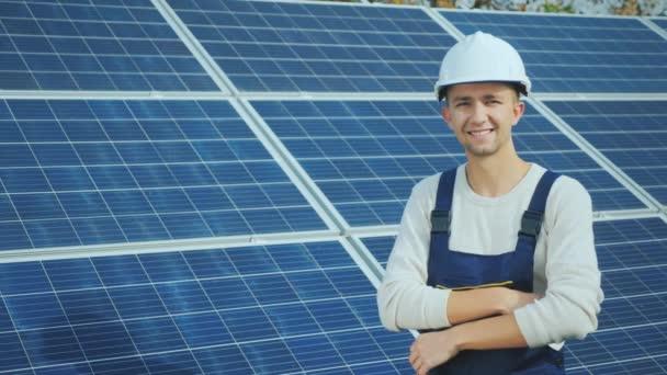 Porträt eines jungen Arbeiters mit weißem Helm auf dem Hintergrund von Sonnenkollektoren