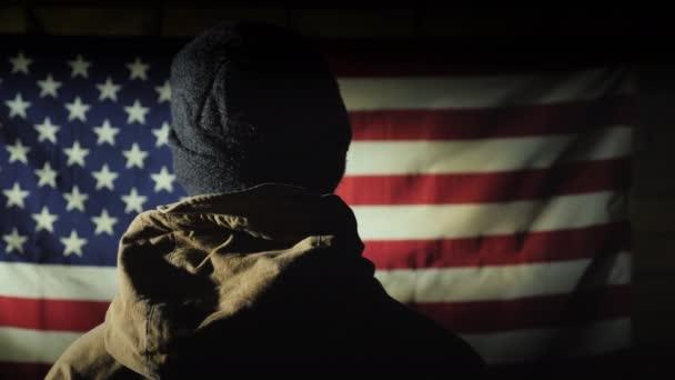 Egy katonai egyenruhás férfi hátulról nézi az amerikai zászlót.