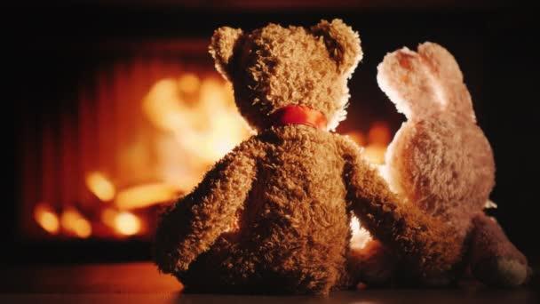 Medve és nyúl egy ölelésben ül a kandalló mellett. Valentin-napi koncepció