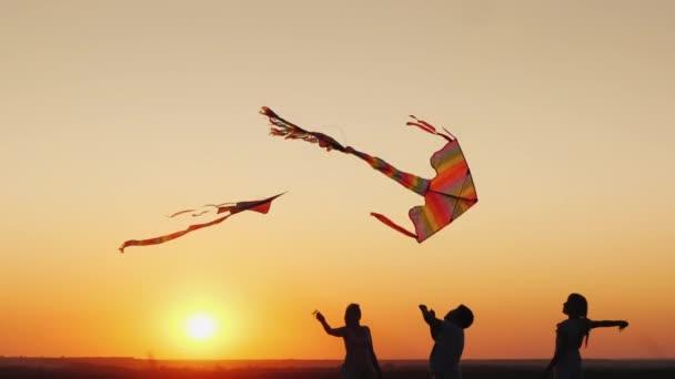 Due bambini con mamma giocano aquiloni al tramonto. Buon tempo insieme