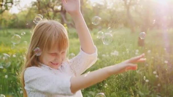 Blondýnka je zábava chytat mýdlové bubliny. Bezstarostné šťastné dítě