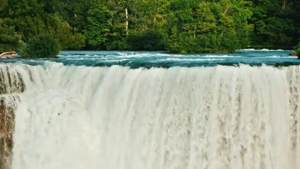 Západ slunce osvětluje Niagarské vodopády a řeku obklopenou lesem. Krásná krajina s americkou přírodou