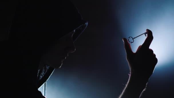 Silueta muže v kapuci s klíčem v ruce. Koncept