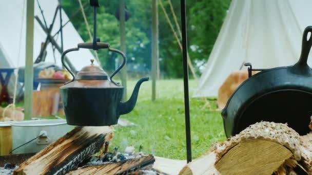 A kanna felforr az amerikai őslakosok táborában az erdőben. Étel készül az előtérben, a hagyományos wigwam sátrak láthatók mögötte.