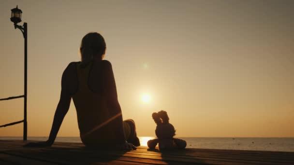 eine Frau mit einem Spielzeugkaninchen sitzt auf einem Steg und bewundert den Sonnenaufgang über dem Meer