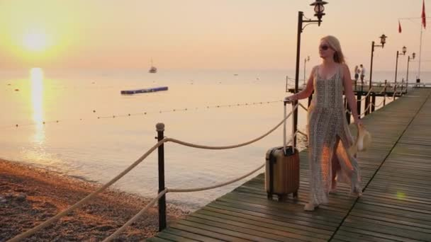 Fiatal boldog turista siet egy település a szállodában, miután találkozott a tutaj a tengeri mólón. Korai bejelentkezés a szállodába