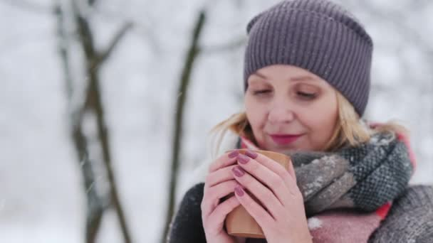 Young woman drinks hot tea from a cup in a winter park