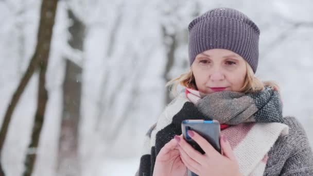 Young woman uses smartphone in snow park
