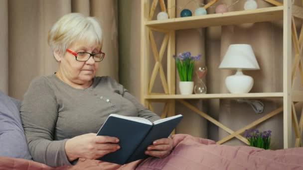 Starší žena s brýlemi čte knihu ve svém pokoji