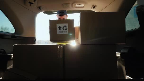 Osoba v masce naloží v kufru auta krabice s léky