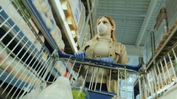 Žena v masce a ochranných rukavicích chodí s nákupním vozíkem v supermarketu. Bezpečné nákupy během karantény