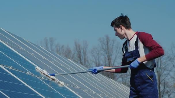 Mann wäscht Sonnenkollektoren im heimischen Kraftwerk