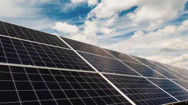Clouds float quickly over solar power plant panels