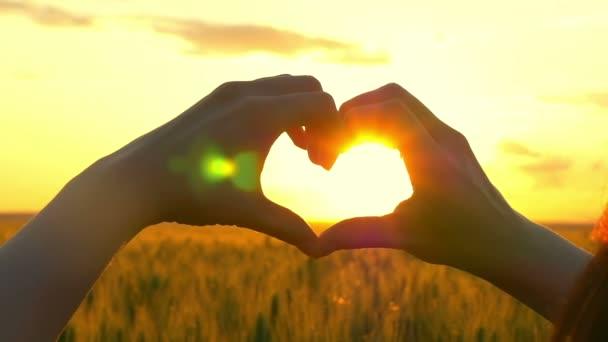 Mladá dívka dělá vlastníma rukama proti ohromující zlatý nebe a vycházející slunce ráno symbolem lásky