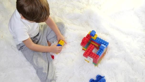 Šťastné dítě hraje v barevné bloky na podlaze na bílém pozadí. Dítě sbírá konstruktor