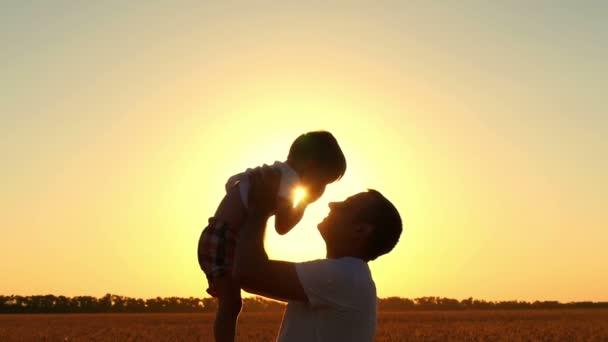 Šťastný tatínek hodí své dítě na pole pšenice před západem slunce. Šťastné tváře a radostné emoce v pomalém pohybu