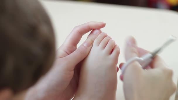 La madre si prende cura di primo piano gambe babys. Mamma taglio unghie sulle gambe del bambino