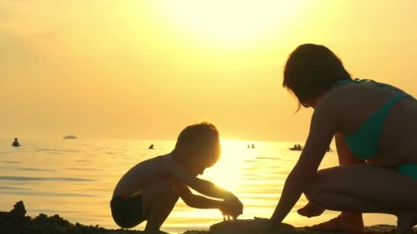 Mother and child playing on the beach in the sand. Mom and child build a sand castle against the background of a sea sunset. The concept of a happy family and rest.