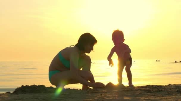 Happy mom and child playing on the beach in the sand. Mom and child build a sand castle against the background of a sea sunset. The concept of a happy family and rest.