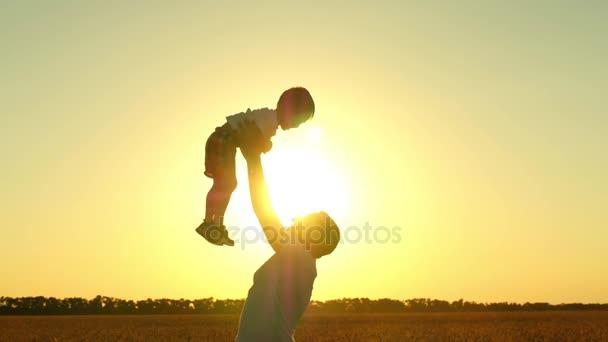 Boldog apa és fia, játszott a természetben a naplemente. Az apa lassú ütemben dob a gyermek, és fogás neki. A koncepció egy boldog család