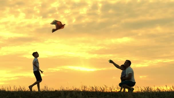 Šťastný otec rodiny a děti běží do oblohy draka v létě při západu slunce v pomalém pohybu. Rodina venku, obloha je žlutá