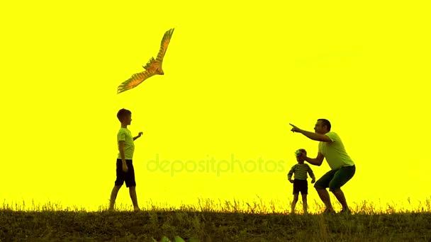 Šťastný otec rodiny a děti běží do oblohy draka v létě při západu slunce v pomalém pohybu. Rodina venku, obloha je žlutá. Žluté pozadí