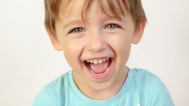 Közeli kép: a gyermek nézett és mosolyogva a lassított kamera. A gyermek azt mutatja, hogy öröm és egy nagy mosoly