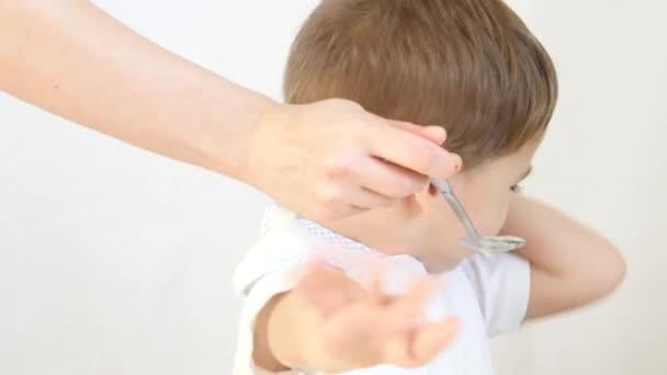Maminka se snaží krmit dítě, ale on odmítá jíst potraviny ze lžíce. Dítě není šťastný a nechce ani jíst. Chlapec nemá rád jídlo